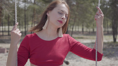 Portrait of elegant beautiful woman in red dress who sit in the forest on the Footage