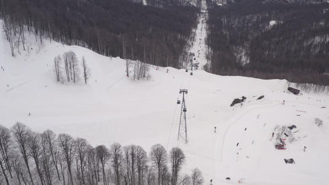 Snowy slope and ski elevator for people transportation on winter resort. Aerial andscape cable way Footage