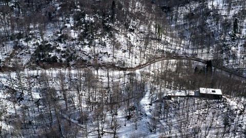 Bare trees on snowy highlands and house view from flying drone. Aerial landscape house in winter Live Action