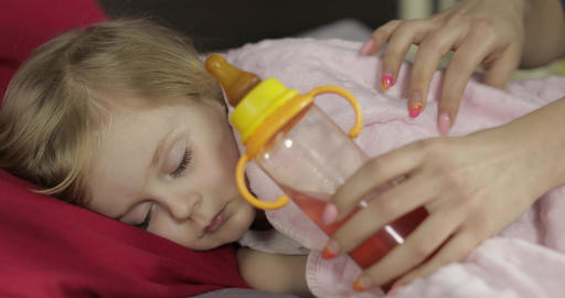 Cute baby girl sleeping on cozy bed at home and drinking juice from bottle Footage