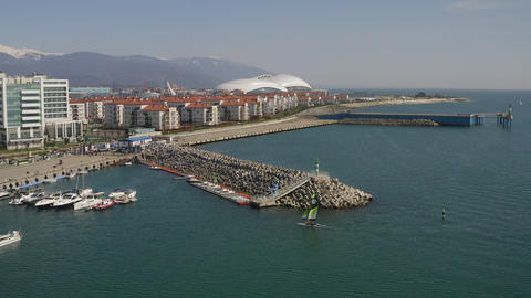 Sailing boat floating in blue sea to pier on modern olympic city view from drone. Sea yacht sailing Archivo