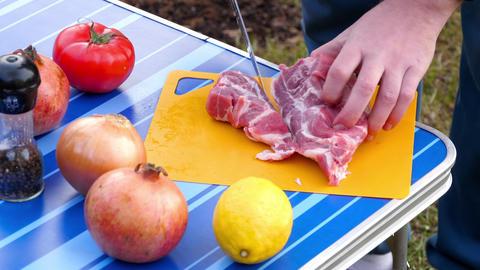 Men slicing meat for BBQ Live Action
