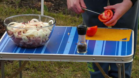 Men slicing tomaytoes for BBQ Live Action