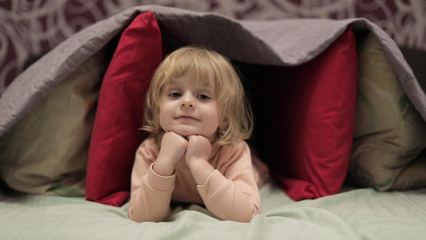 Little girl hides under blanket and pillows on the bed. Concept of hiding place Footage
