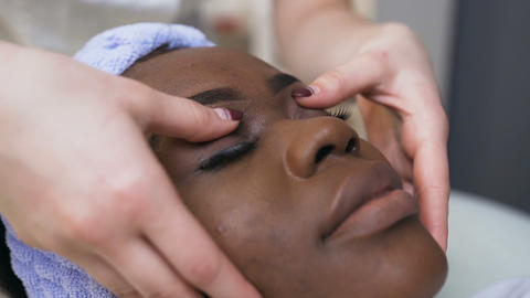 Female beautician hads making massage on african female face and eyes Live Action