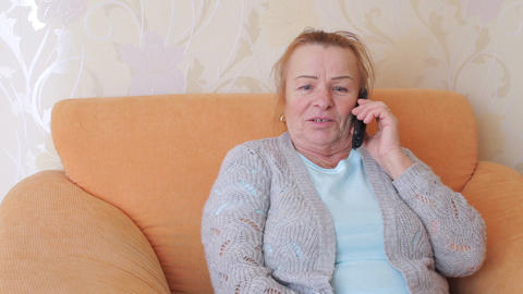Mature emotional woman talking on the phone Live Action
