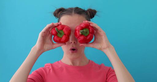 Woman wonders holds pepper in her hands like eyes Archivo