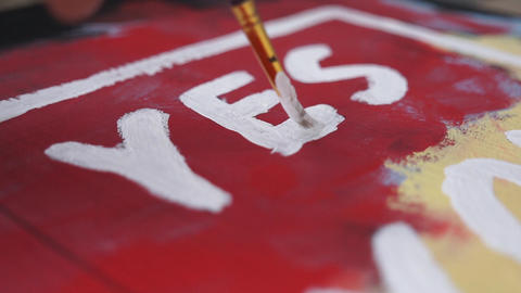 """Writing the word """"Yes"""" with a brush on a wooden board. Red background, white Live Action"""