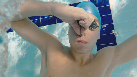 Guy swimmer underwater holding his breath blowing out air rings Footage