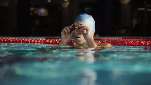 Portrait of a male swimmer puts on swimming goggles Footage