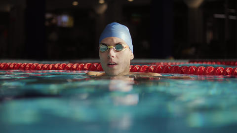 Portrait of a male swimmer puts on swimming goggles Stock Video Footage