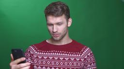Happy young brunette businessman talking in videochat on cellphone being joyful Footage