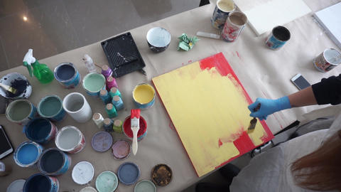 The artist paints a wooden board. Red and yellow paint. Art Studio. Paint cans Footage