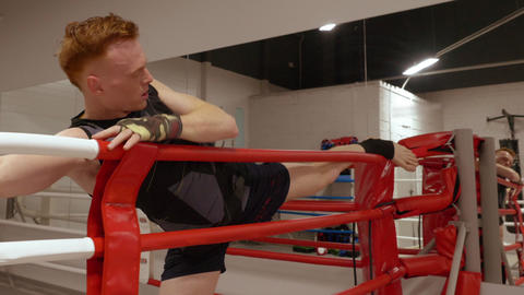 Man boxer stretching leg before boxing training on box ring in fight club Live Action