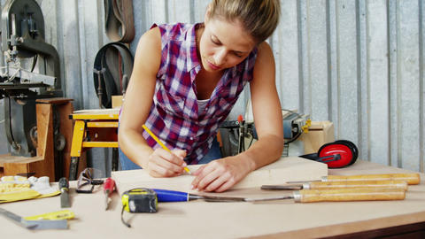 Focused carpenter marking a wooden plank with pencil Live Action