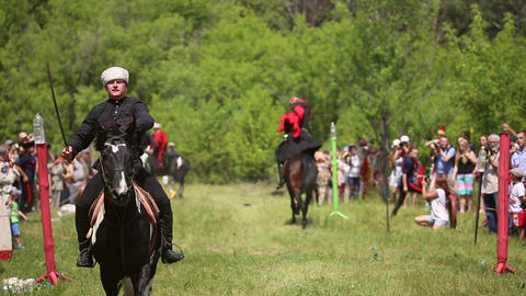 Riders riding on horses, they saber cuts water bottles Footage