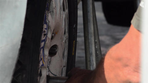 Auto mechanic who check the wheels of a racing car before a competition 03 Footage