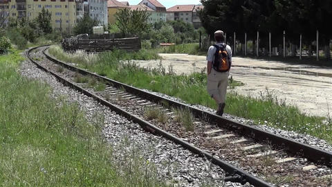 Man walking along the railroad along which grew weeds at the edge of a neighborh Footage