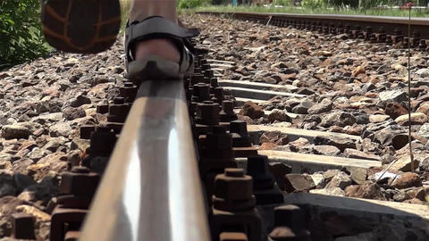 Sandals feet of a man walking down a railroad track in balancing 11 Footage