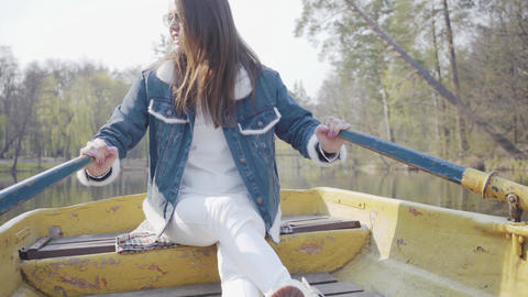 Pretty smiling glamour woman in white pants, jeans jacket and sunglasses paddles Live Action