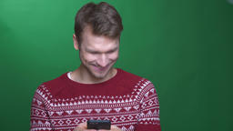 Happy young brunette businessman working with cellphone and smiling into camera Footage