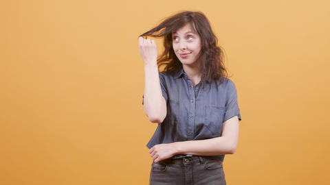 Young pretty girl smiling and playing with her hair over a yellow background Footage