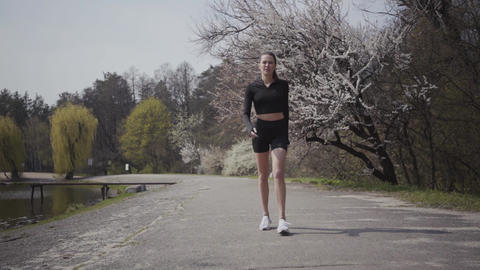 Slim sports young woman in sportswear running on the riverbank. Active lifestyle Footage