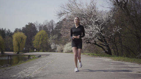 Slim sports young woman in sportswear running on the... Stock Video Footage