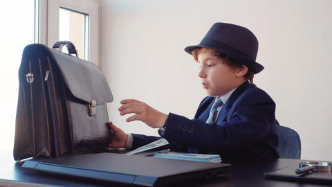 Little boy business boss at business table hiding money stack in briefcase in Footage