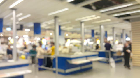 Blurred scene. People, costumers are checking out at the cashier in a store or a supermarket. Footage