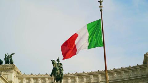 Slow motion shot of waving flag of Italy on Vittorio Emanuele palace background Live Action