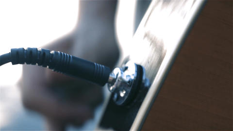 Male Hand Plugging Cable Jack In Electric Guitar. Close-Up Live Action