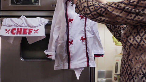 Woman Picking Up A Chef Uniform In The Kitchen. Zoom In Footage
