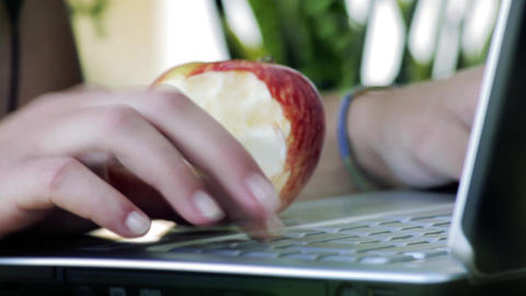 Woman Eating Apple While Works On Laptop Computer GIF