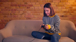 Closeup portrait of young pretty girl playing video games using the game console Footage