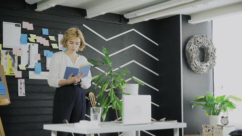 Casual Young Girl Reading Book in Creative Workplace Footage