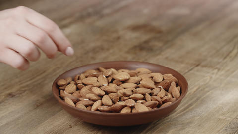 Woman Picks Up A Single almond, To Eat, From Her Bowl. took a nut on the left Live Action