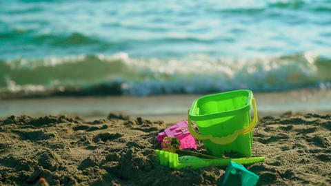 Toy shovel on sea beach. Summer day family concept. Holiday relax. Slow motion Footage