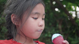 Asian little girl eating an ice cream outdoors Footage