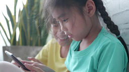 Asian children's little girls using smart phone at home Footage