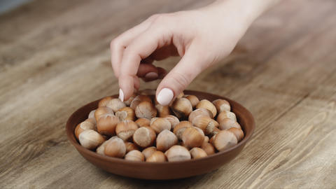 Woman Picks Up A Single Hazelnut, To Eat, From Her Bowl. took a nut on the right Footage