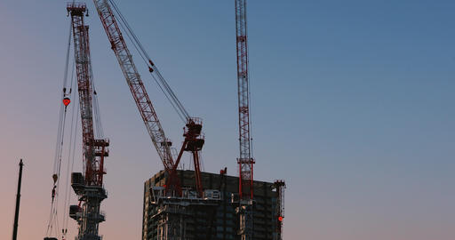 Cranes at the under construction in Tokyo wide shot at dusk Footage