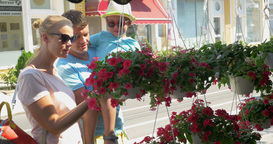 Parents and son looking at flowers in the street Footage