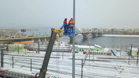 Electricians worked at autotower. Workers repair mast lighting. Aero view Footage