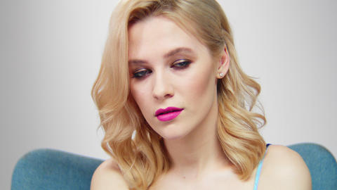 blond woman with stylish makeup sits in cozy armchair GIF