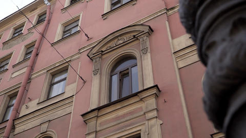 Scenery of old pink historical building with several windows on sunny day Live Action