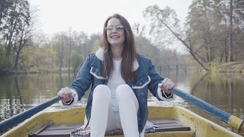 Pretty young glamour woman in white pants, jeans jacket and sunglasses paddles Live Action