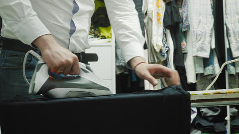 Man ironing black t-shirt standing in the dressing room Footage