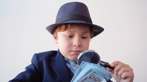 Focused business boss checking money banknotes with magnifying glass in office Archivo