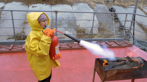 Female firefighter in protective uniform extinguishes flame with extinguisher in Live Action